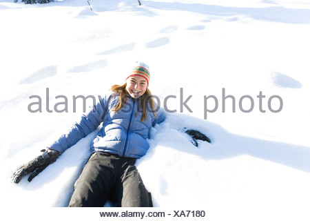 Young woman on snowshoes plays in snow near Homer, Alaska during winter. - Stock Photo