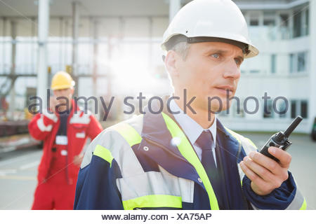 Male worker using walkie-talkie with colleague in background at shipping yard - Stock Photo