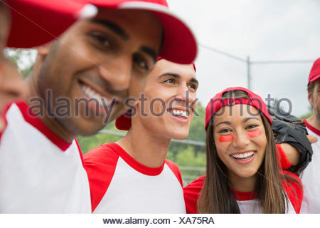 Baseball team laughing together in field - Stock Photo