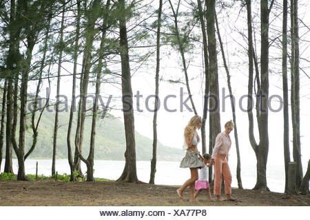 Two women holding hands with small girl - Stock Photo