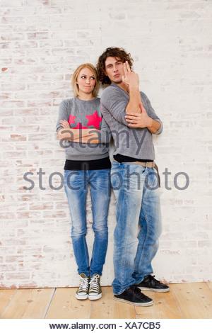 Studio portrait of couple making gun hand gestures - Stock Photo