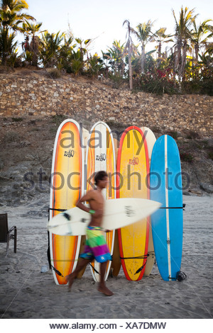 A surfer runs to the waves next to a stack of boards at Los Cerritos near Pescadero, Mexico. - Stock Photo