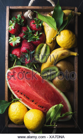 Various colorful tropical fruit selection in wooden tray over dark background, top view. Watermelon, strawberry, lemons and kiwi - Stock Photo