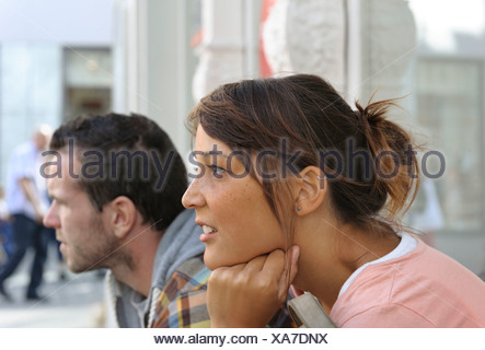 A young couple sitting side by side, looking in the same direction, Konstanz or Constance, Baden-Wuerttemberg, PublicGround - Stock Photo