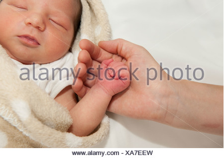 Mother's hand holding little hand of newborn baby