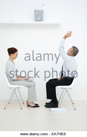 Professionals sitting face to face, man tossing paper ball into wastebasket, woman using laptop - Stock Photo