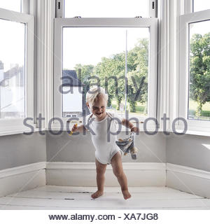 Boy dancing in living room holding toy - Stock Photo