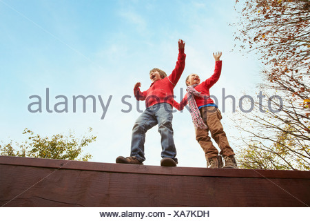 Children balancing on wooden wall - Stock Photo
