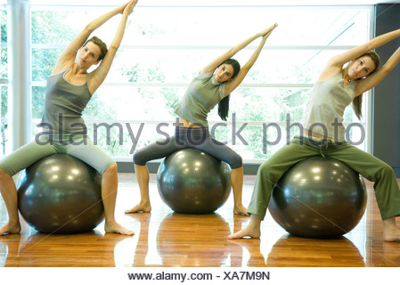 Exercise class doing side stretch on fitness balls - Stock Photo