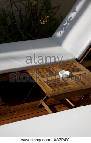 Ashtray on table between lawn chairs - Stock Photo