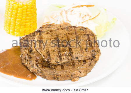 Grilled rib eye steak, corn on the cob and salad close up - Stock Photo