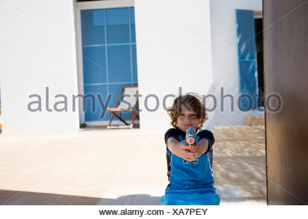 Boy holding up squirt gun - Stock Photo