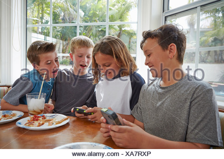 Boys playing handheld video games - Stock Photo