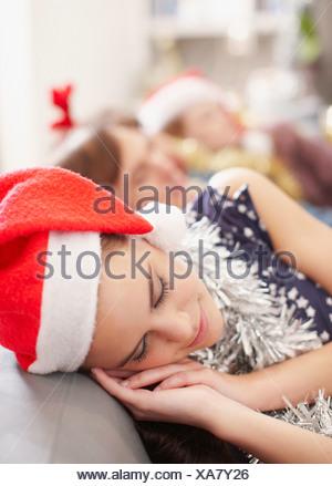 Woman in Santa hat sleeping on sofa - Stock Photo