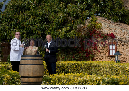 Winemaker Prof. Michael Popp, left, Herta and Peter Himbert, owners of the Molí des Torrent restaurant, Santa María del Camí - Stock Photo