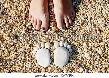 Croatia, Stones in shape of feet in front of woman's feet - Stock Photo