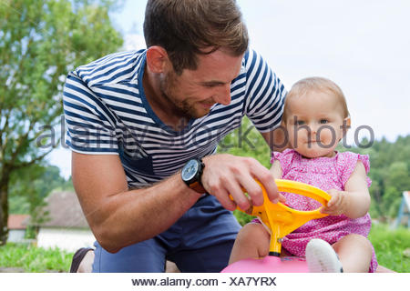 Mid adult man with baby daughter on toy car in garden - Stock Photo