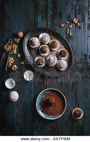 Variety of homemade dark chocolate truffles with cocoa powder, coconut, walnuts on vintage tray over old dark blue wooden background. Top view, space. - Stock Photo