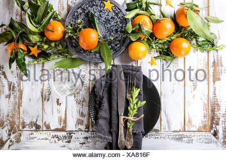 Christmas table decorations with clementines or tangerines with leaves and green branches on black ornate board. Empty plate with cutlery and textile  - Stock Photo