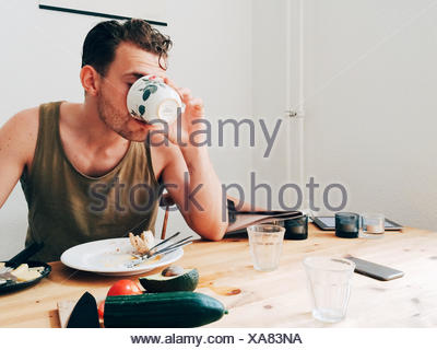 Man Drinking Coffee By Messy Table - Stock Photo