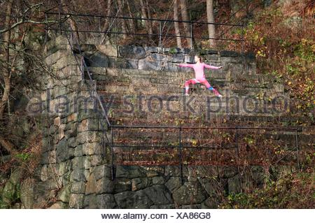 Young woman doing stretching exercises on overgrown stone steps - Stock Photo