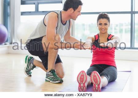 Male trainer assisting woman with pilate exercises in fitness studio - Stock Photo