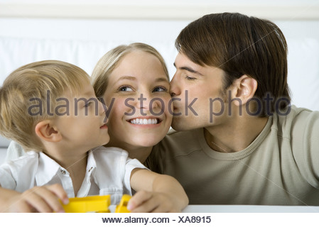 Man kissing wife on the cheek, young son watching - Stock Photo