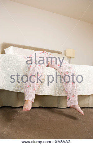 Legs of woman in pajamas hanging off bed - Stock Photo
