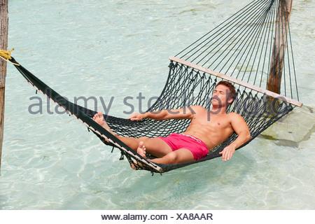 Man Relaxing In Beach Hammock - Stock Photo