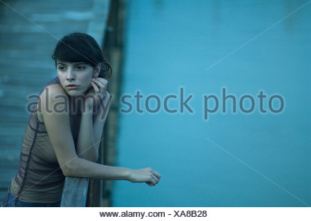 Woman leaning on railing of pier, looking away - Stock Photo