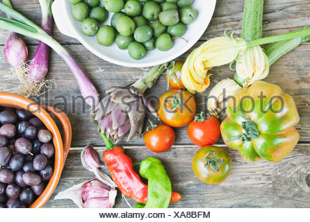taly, Tuscany, Magliano, Olives in bowl, spring onions, tomatoes, garlic, peppers and artichoke on wooden table - Stock Photo