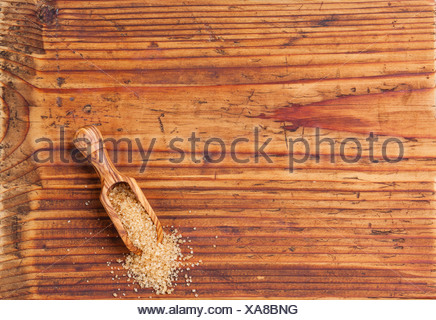 Cane sugar in wooden scoop on wooden background - Stock Photo