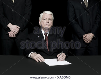 Politician signing paper - Stock Photo