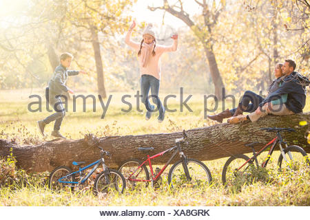 Family playing on fallen log in autumn woods - Stock Photo