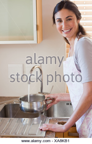 Portrait of a woman pouring water in a sauce pan - Stock Photo
