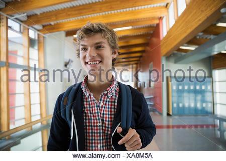 Smiling high school student in corridor - Stock Photo