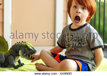 Boy playing with toy dinosaur, pretending he's been bitten - Stock Photo