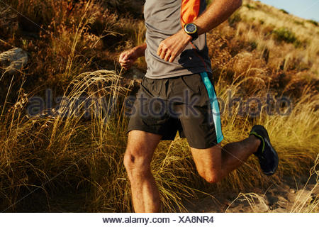 Man running on trail through tall grass - Stock Photo