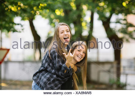 Portrait of young woman giving friend piggy back in park - Stock Photo