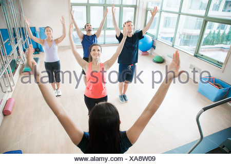 Young people with hands in the air in a yoga class - Stock Photo