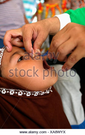 Vitamin A given to a young girl after the Indian Ocean tsunami in 2004; Banda Aceh, Aceh Province, Sumatra, Indonesia - Stock Photo