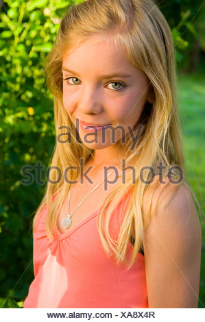 Close-up portrait of a blonde teenage girl with green eyes smiling - Stock Photo