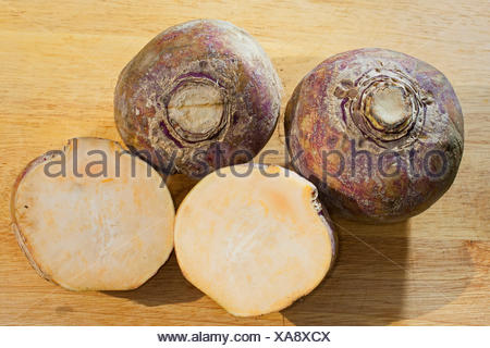 rutabaga, swede, turnip, yellow turnip, neep, root, beet (Brassica napus subsp. rapifera, Brassica napus rapifera, Brassica rapifera), three harvested rutabagas, one of them halved, Germany - Stock Photo