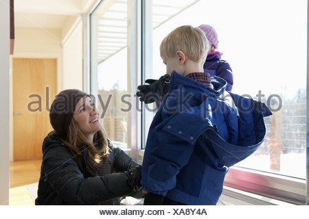 Boy getting dressed in winter clothing, mother helping - Stock Photo