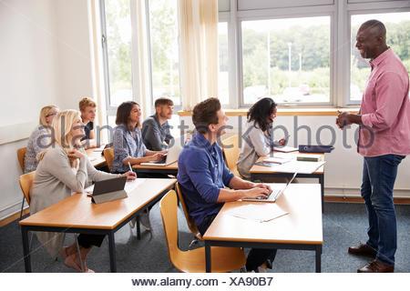 Male Tutor Teaching Class Of Mature Students - Stock Photo