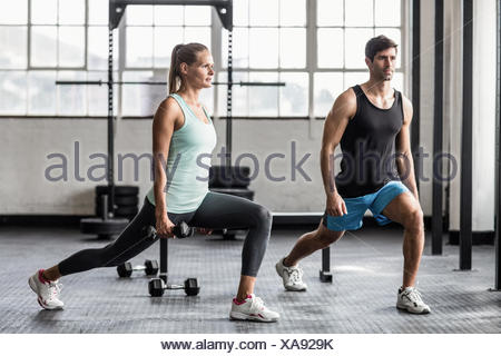 Male trainor with woman using dumbbells exercising - Stock Photo