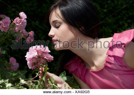 Woman smelling flowers outdoors - Stock Photo