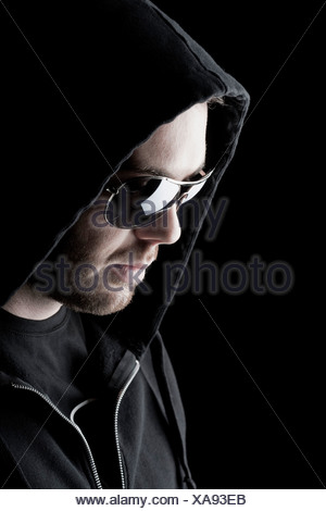 Man wearing sunglasses and a hood, Innsbruck, Tyrol, Austria - Stock Photo
