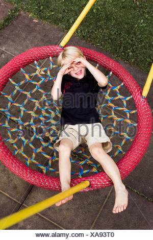 Portrait of little boy relaxing on playground equipment shielding his eyes with his hands - Stock Photo