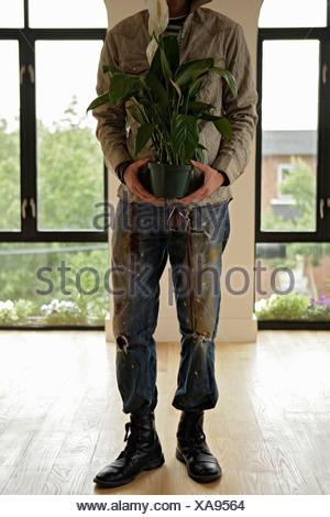 Man holding flowerpot, cropped - Stock Photo